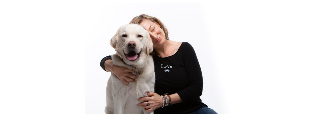 Positivity Designs Founder wearing Love T-shirt and hugging dog